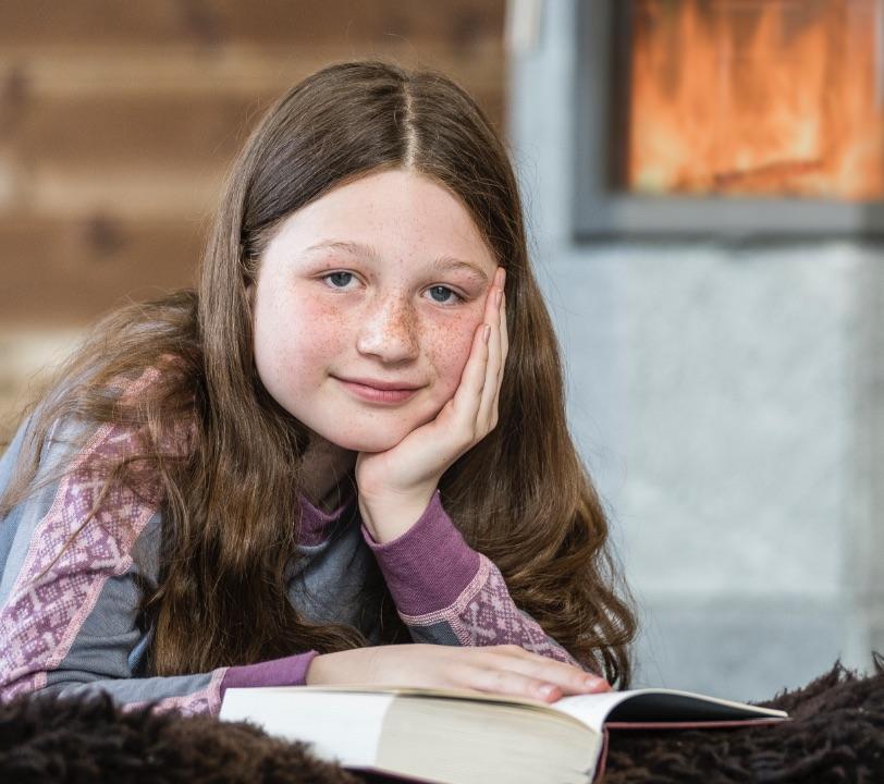 Meisje met op de achtergrond een speksteenkachel van Norsk Kleber