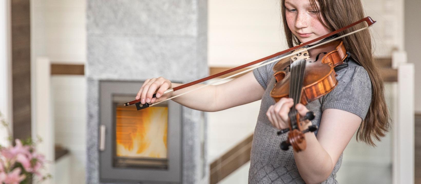 Sfeerbeeld van meisje dat viool speelt in een kamer verwarmd door een Norsk Kleber kachel